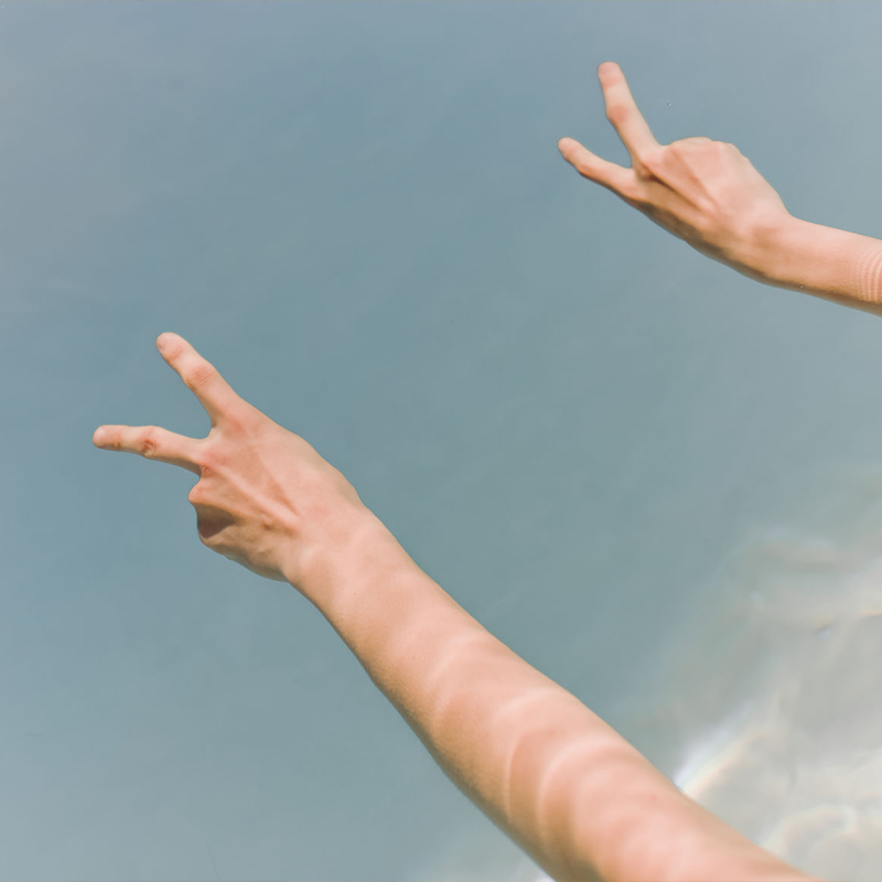 Two arms extended and making peace gesture with hands