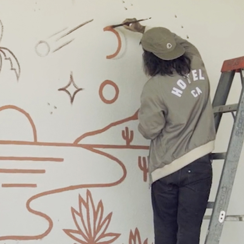 Man standing on stepladder, painting a wall