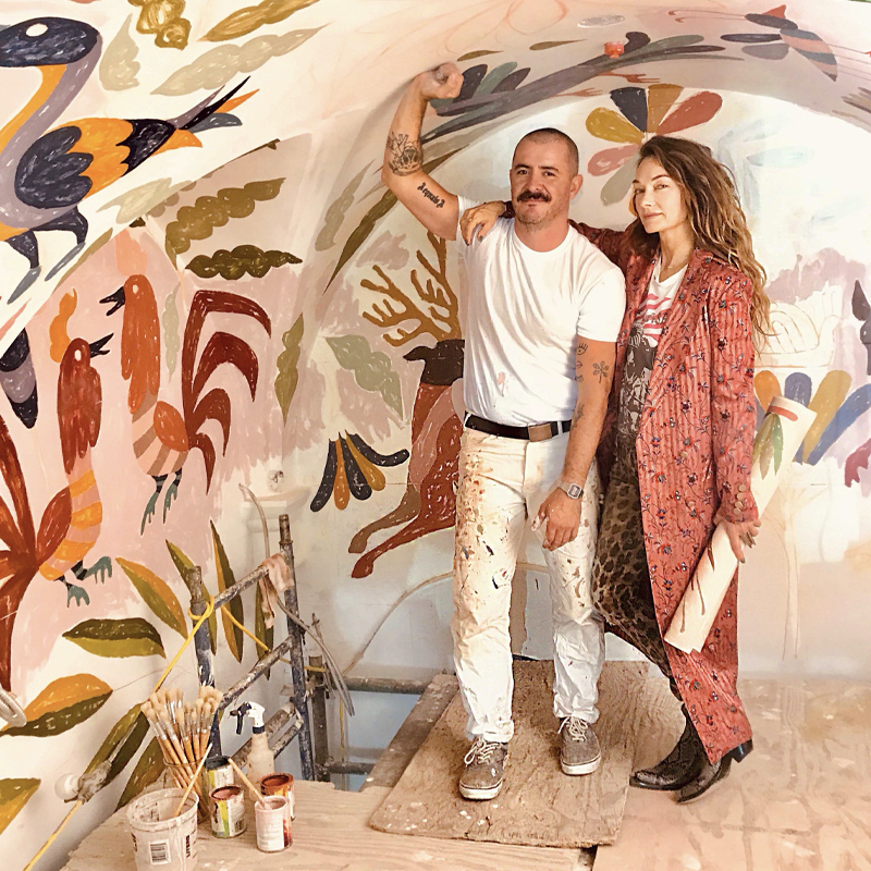 Painter and woman standing next to curved ceiling with painted artwork