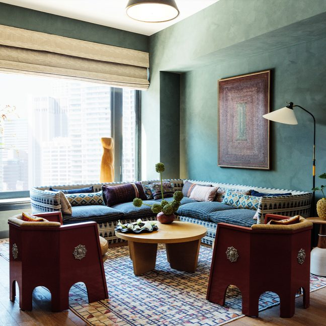 Living room area with sectional sofa, chairs, coffee table, and large window with view of Downtown LA buildings