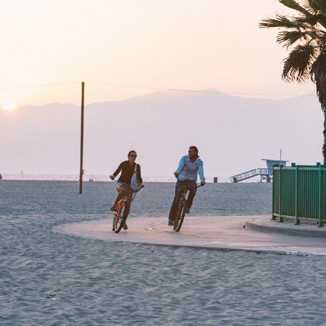 Couple riding bikes on wide sidewalk next to beach