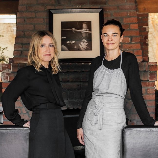 Two women standing in front of brick chimney and framed photo art hanging above chimney